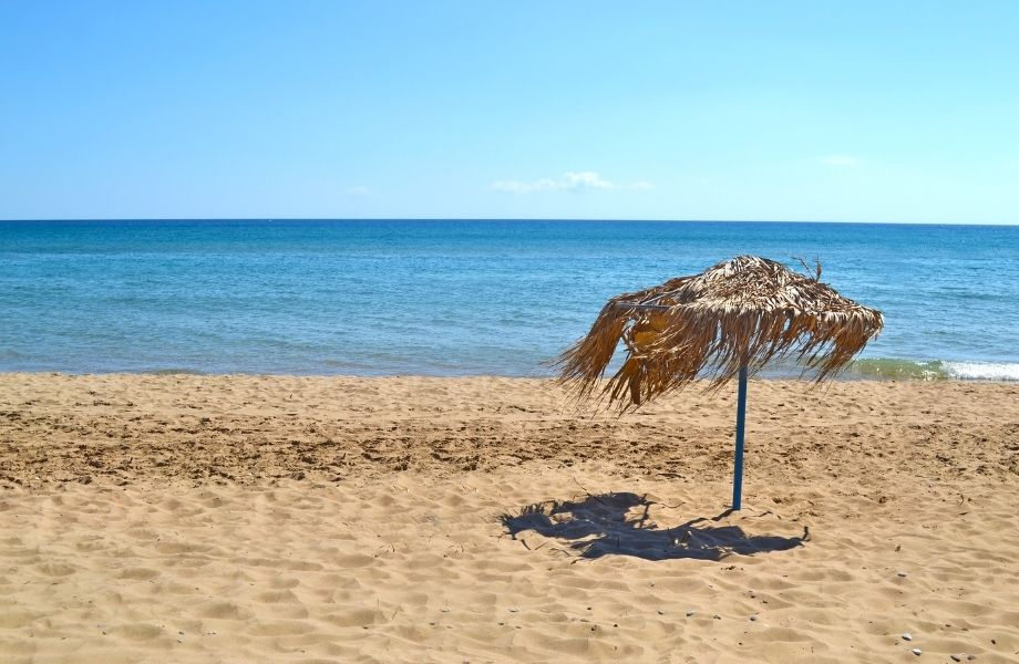 best Paros beaches, straw umbrella blowing in the wind on Glyfa Beach