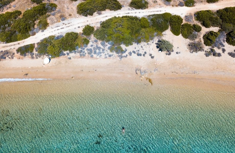 nude beach Paros, aerial view of person swimming in the clear waters of Lageri Beach
