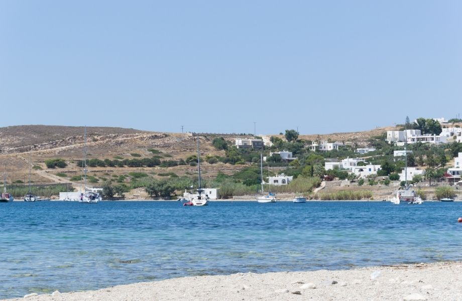 Must See Beaches in Paros Greece, Livadia Beach with boats on the water and white square homes in the hills