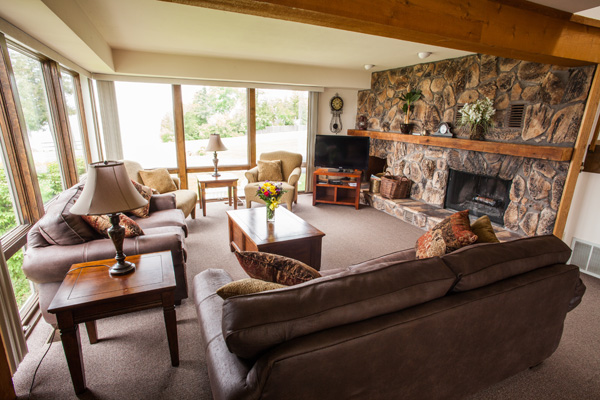Best lakeside resorts in Door County Wisconsin, large living room area with two sofas, two chairs, coffee table, tv, fireplace and bay windows