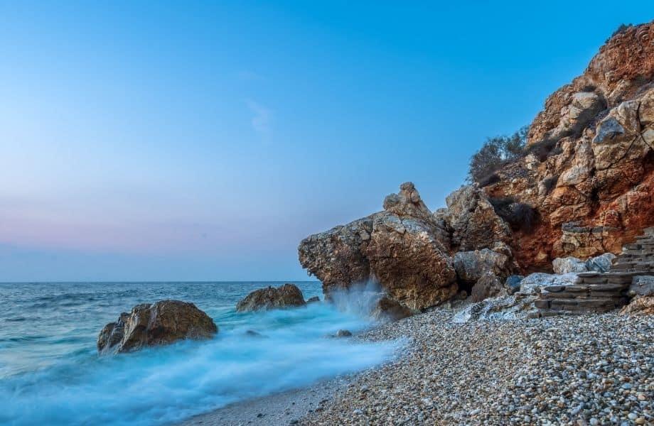 Paros' best beaches, water hitting the rocks along the coast of Piso Livadi Beach