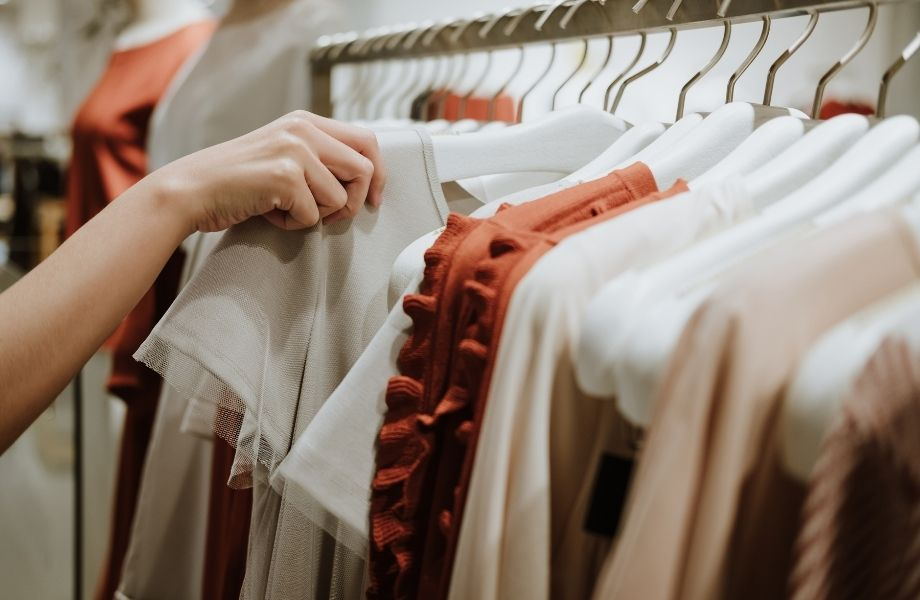 best sustainable vegan clothing brands, person pulling a shirt of the rack