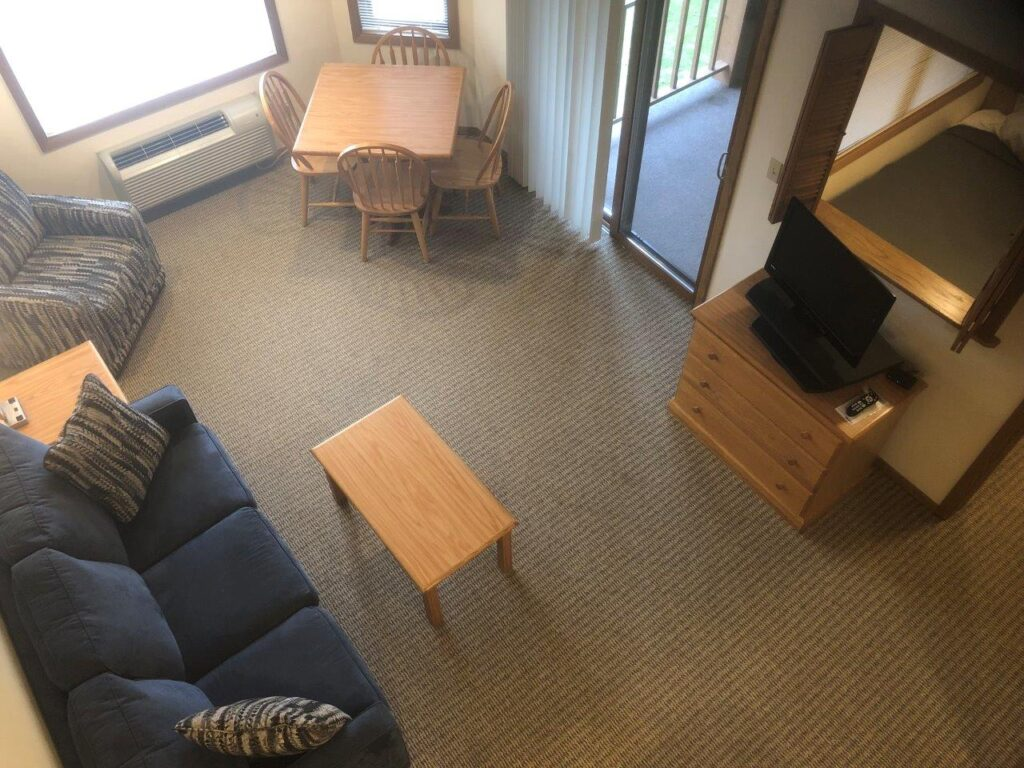 best places to stay in Door County for families, aerial view of room showing sofa, coffee table, tv and bed