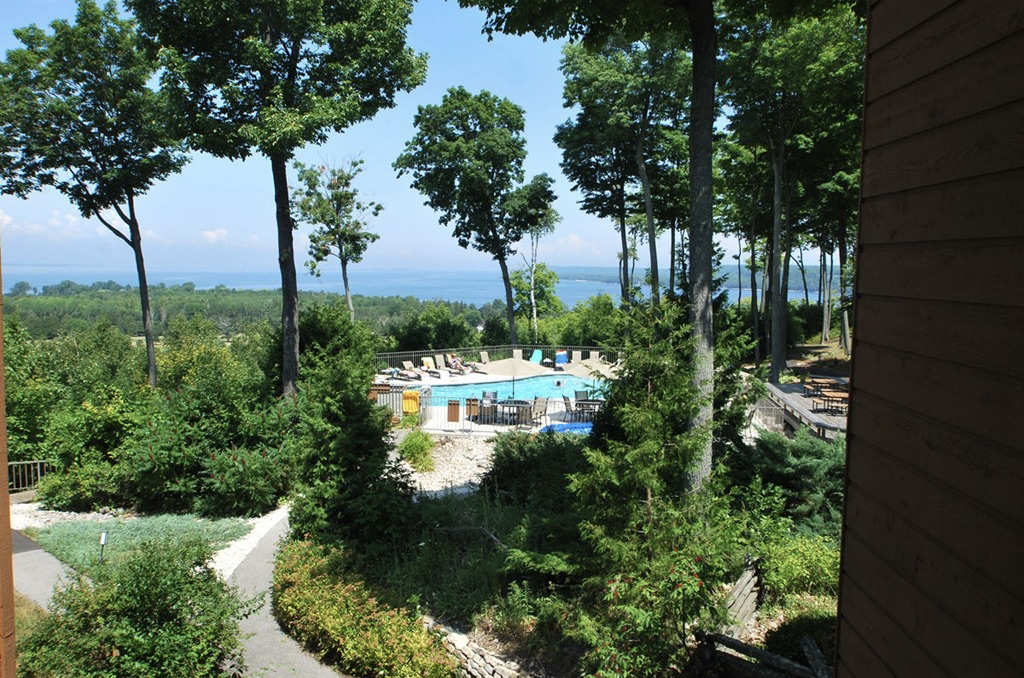 best places to stay in Egg Harbor, view from hotel room of the pool surrounded by trees and lake in distance