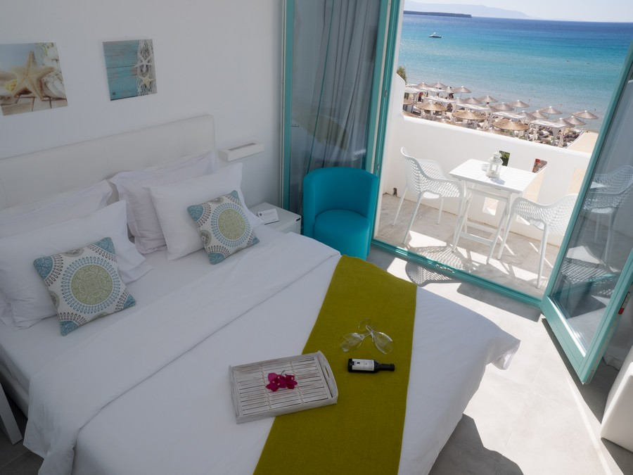 best resorts in paros greece, room with balcony overlooking beach and beach umbrellas at Amaryllis Beach Hotel