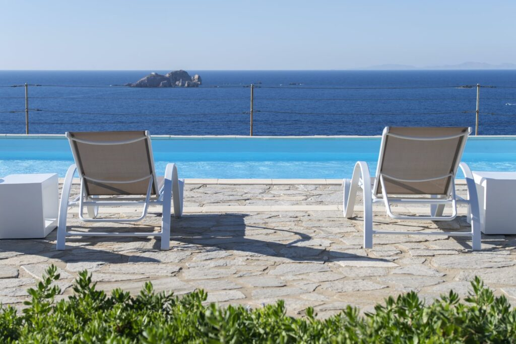 Best Resorts in Paros for Every Budget, two beach chairs overlooking pool and ocean at Archipelagos Resort & Villas
