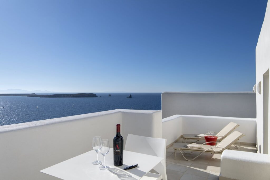 top hotels in Paros, balcony with deck chairs and table with wine bottle and glasses overlooking ocean
