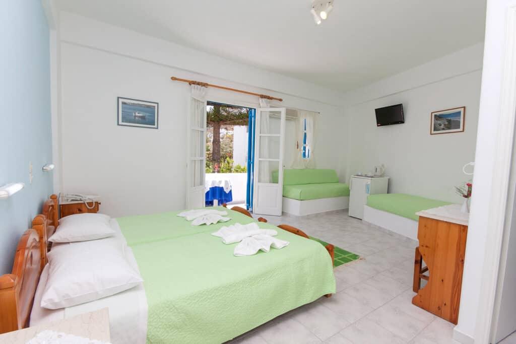 best Paros Greece resorts, room at Ayeri hotel with three beds, sofa, fridge and desk