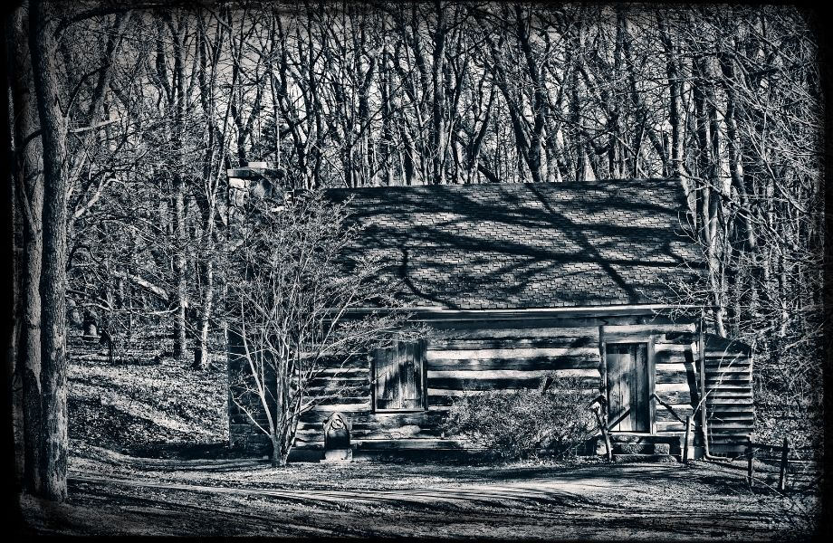 black and white photo of a cabin in the woods; get locked in a creepy cabin at one of the best escape rooms in Wisconsin Dells