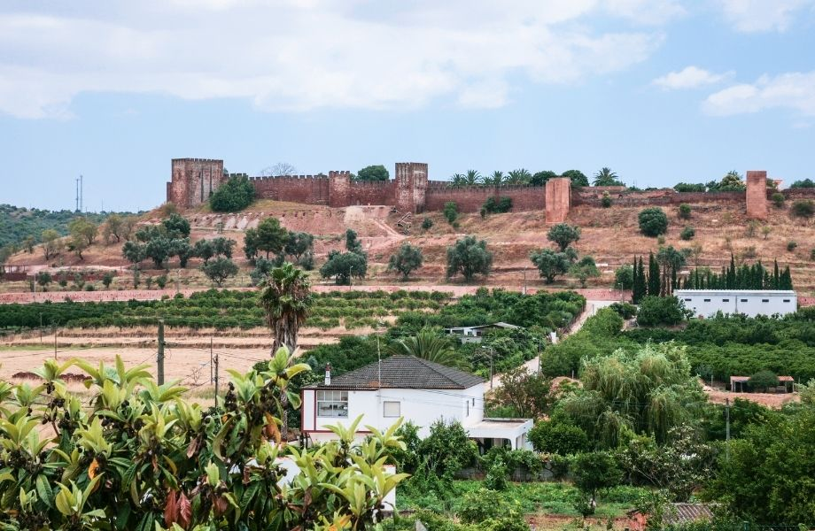 things to do in algarve with family, ruins of the castle of silves in distance behind homes and greenery