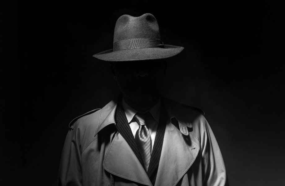 man in jacket with hat hiding his face in shadow; enjoy a film noir puzzle at the Appleton escape room