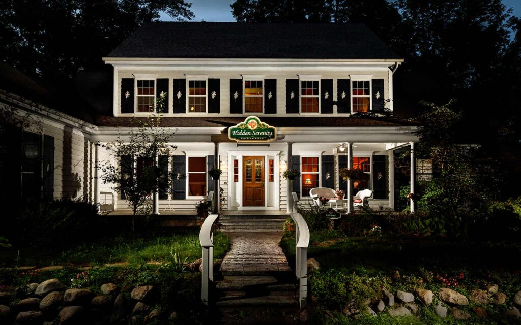 best spa resorts in Wisconsin for couples, exterior view of Hidden Serenity Bed and Breakfast with seats outside and lots of foliage