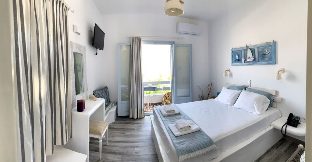 boutique hotels Greece, room with bed, desk, seating area and boat art above bed, balcony overlooking garden