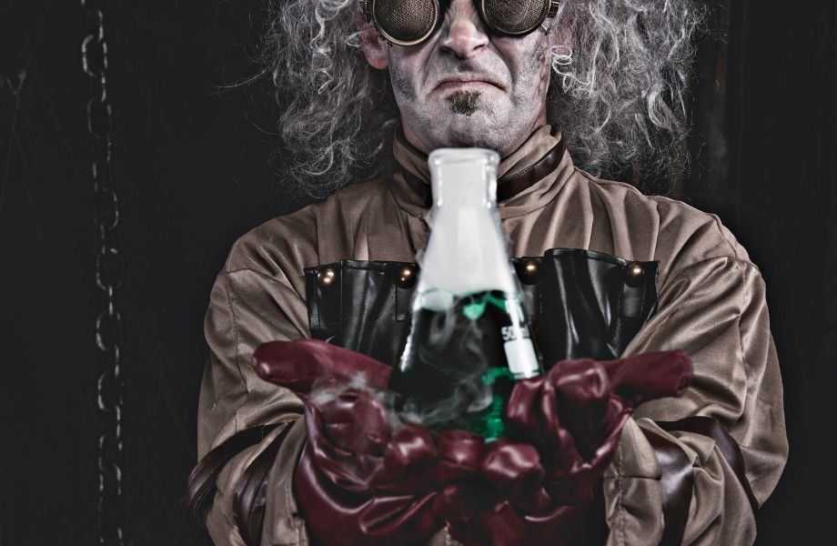 man with safety googles and gloves holding out foggy liquid in bottle; get locked up by a mad scientist at one of the Madison escape rooms