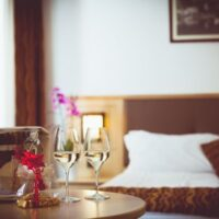 Most Romantic Hotels in Wisconsin, table with wine in ice bucket, chocolates and two wine glasses with bed in background