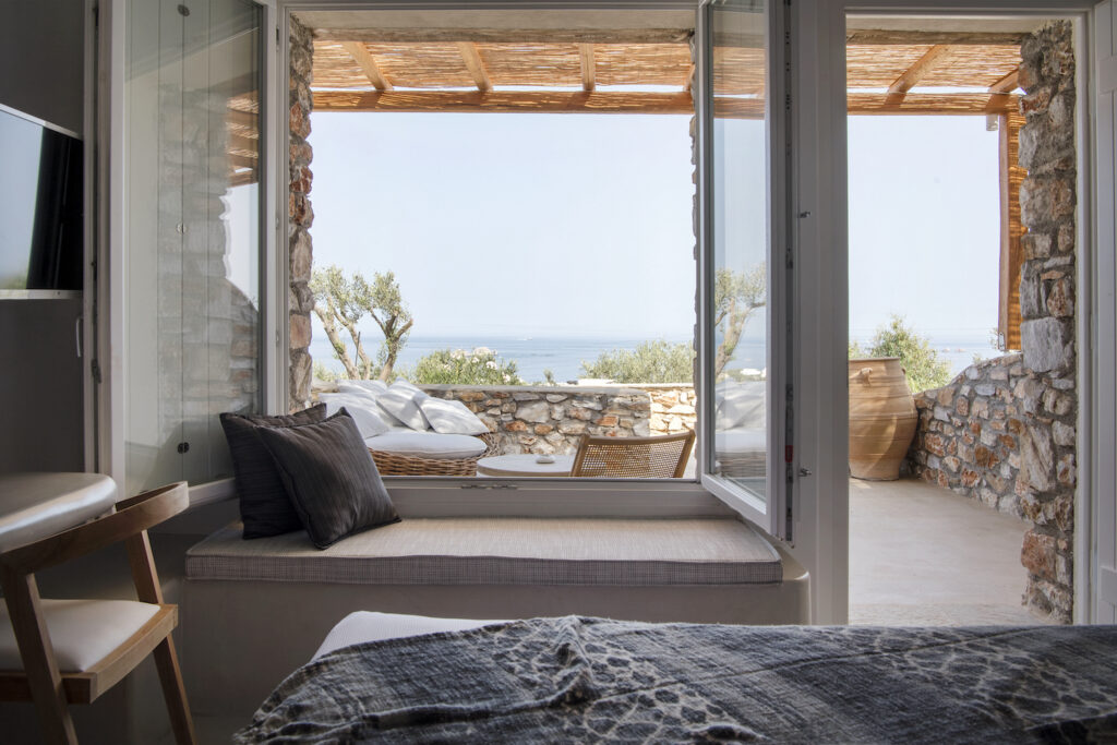 luxury resorts in Paros Greece, room with bed, desk, and large outdoor seating area at the adults only Mythic Exclusive Retreat