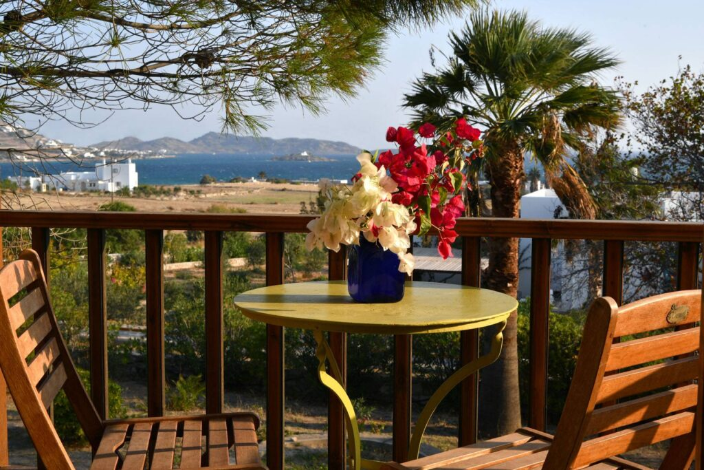 amazing accommodation in Paros Greece, table and chairs on balcony overlooking town and beach