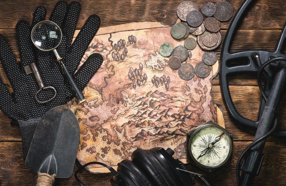 treasure map with old coins, compass, shovel and other tools; escape the room in Milwaukee has an Indiana Jones themed room