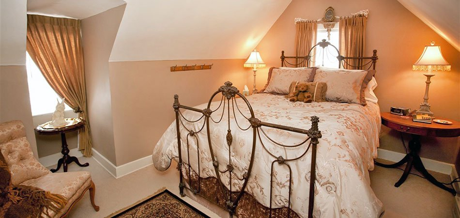 best Wisconsin getaways for couples, bedroom with slanted roof, bed has thick sheets and a teddy bear on top