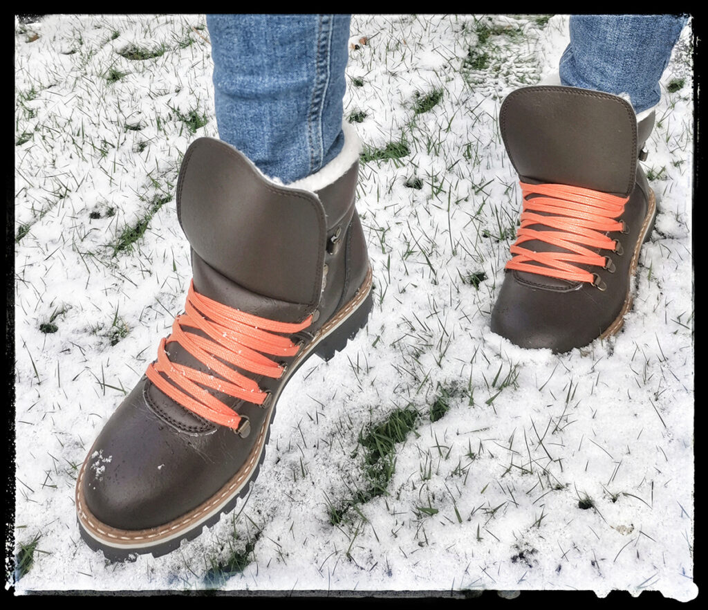 warm vegan winter boots for women, person walking in snow in brown winter boots with orange laces